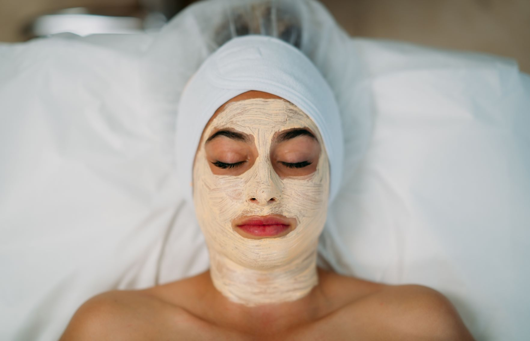 Client laying down with their eyes closed while receiving a facial treatment mask.