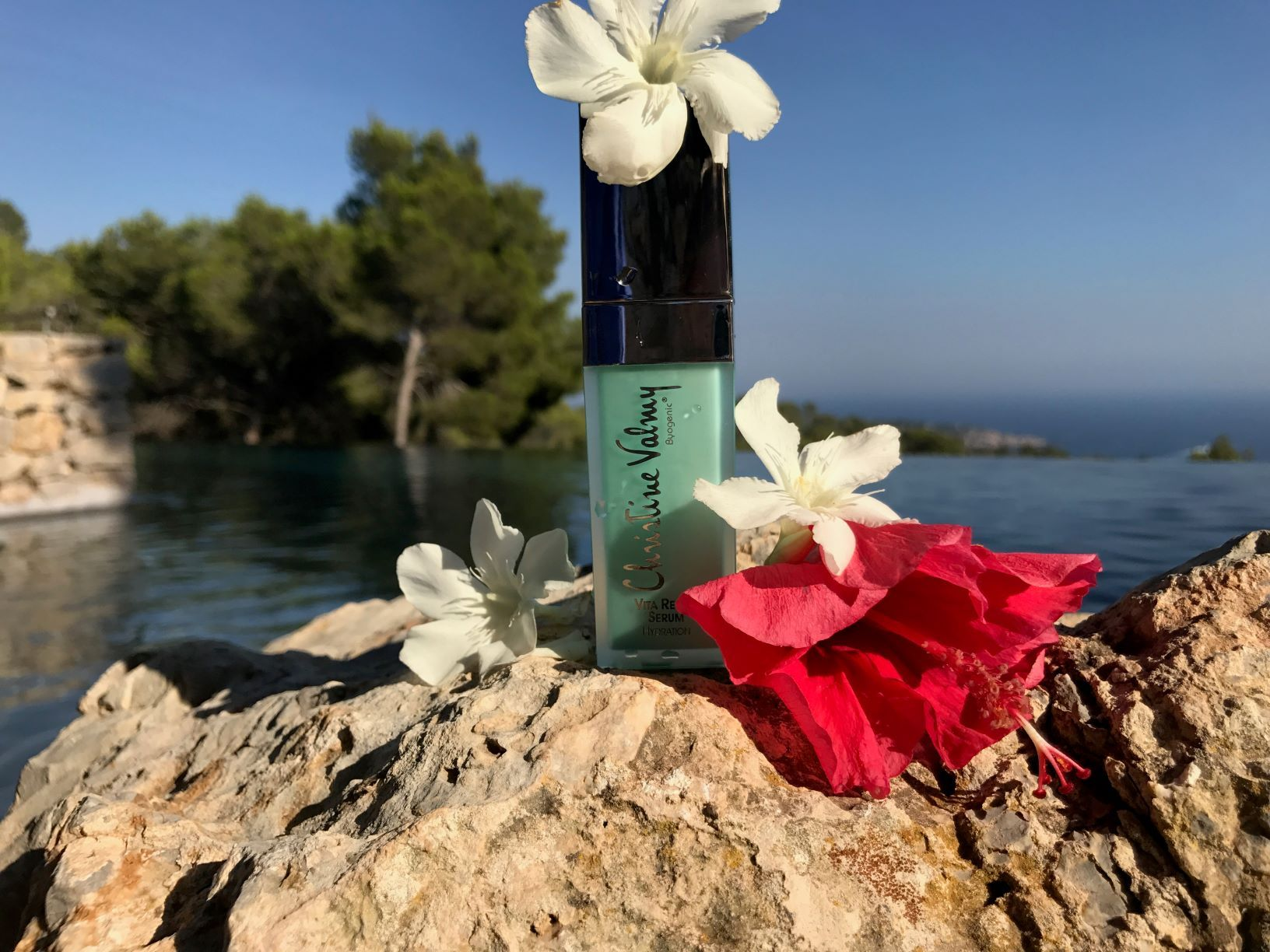 Christine Valmy Skin Care Product on rocks, surrounded by flowers, in front of a body of water.