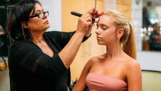 Makeup instructor applying makeup to demonstrate application techniques.