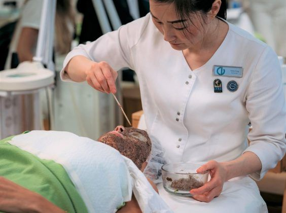 Christine Valmy esthetics instructor applying an all-natural face mask on a client laying down.