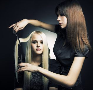 Woman holding scissors up to another woman's hair extensions.