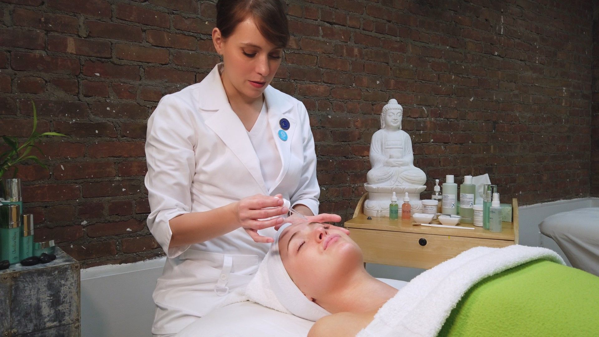 Christine Valmy instructor applying a serum to a student laying down