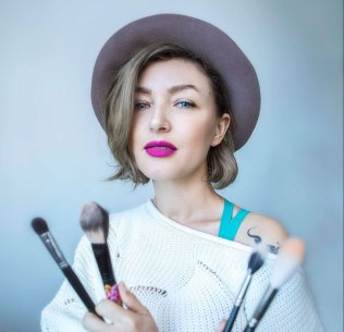 Christine Valmy makeup instructor holding makeup brushes