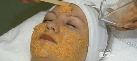 Marina Valmy applies a DIY facial mask to a client laying on a spa treatment bed